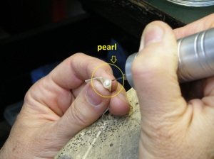 "Holding a pearl with a masking tape ""handle"" to drill it."